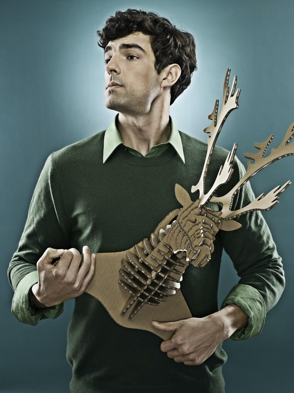 man wearing green sweater holding brown deer head decor