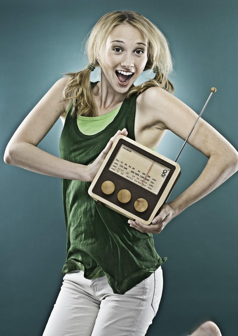 smiling woman holding brown transistor radio