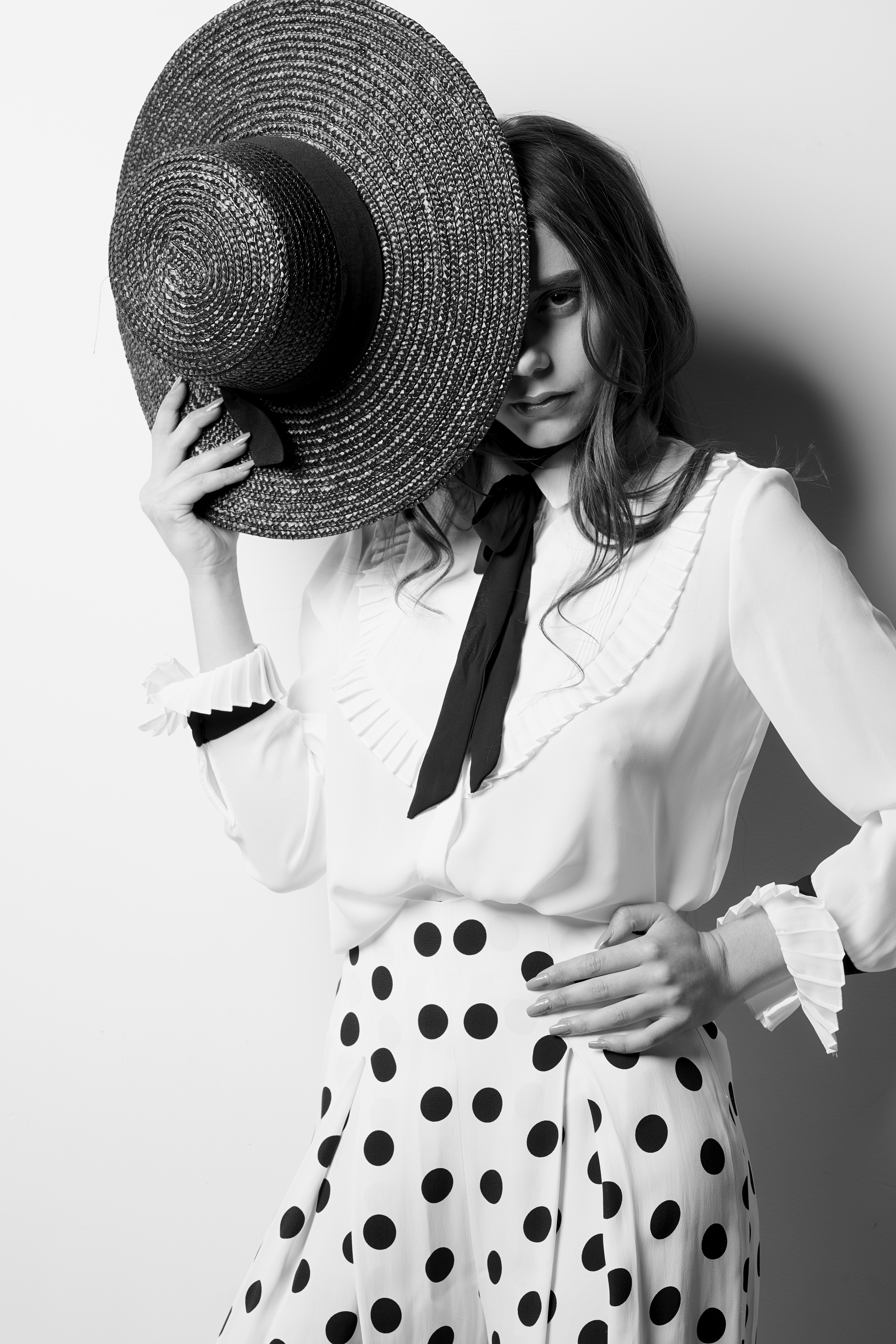 grayscale photo of woman holding hat