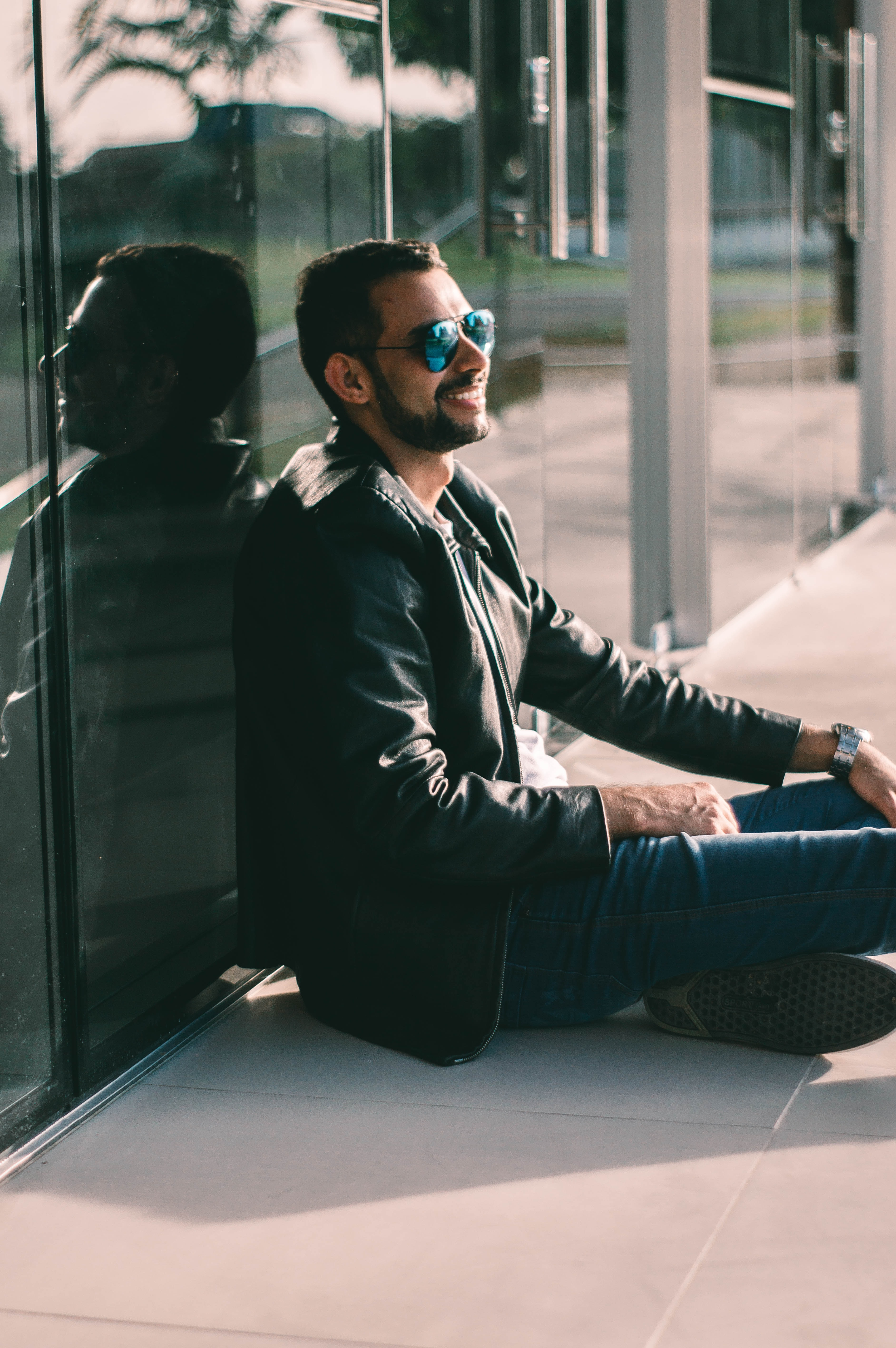 man sitting on floor while leaning on glass wall