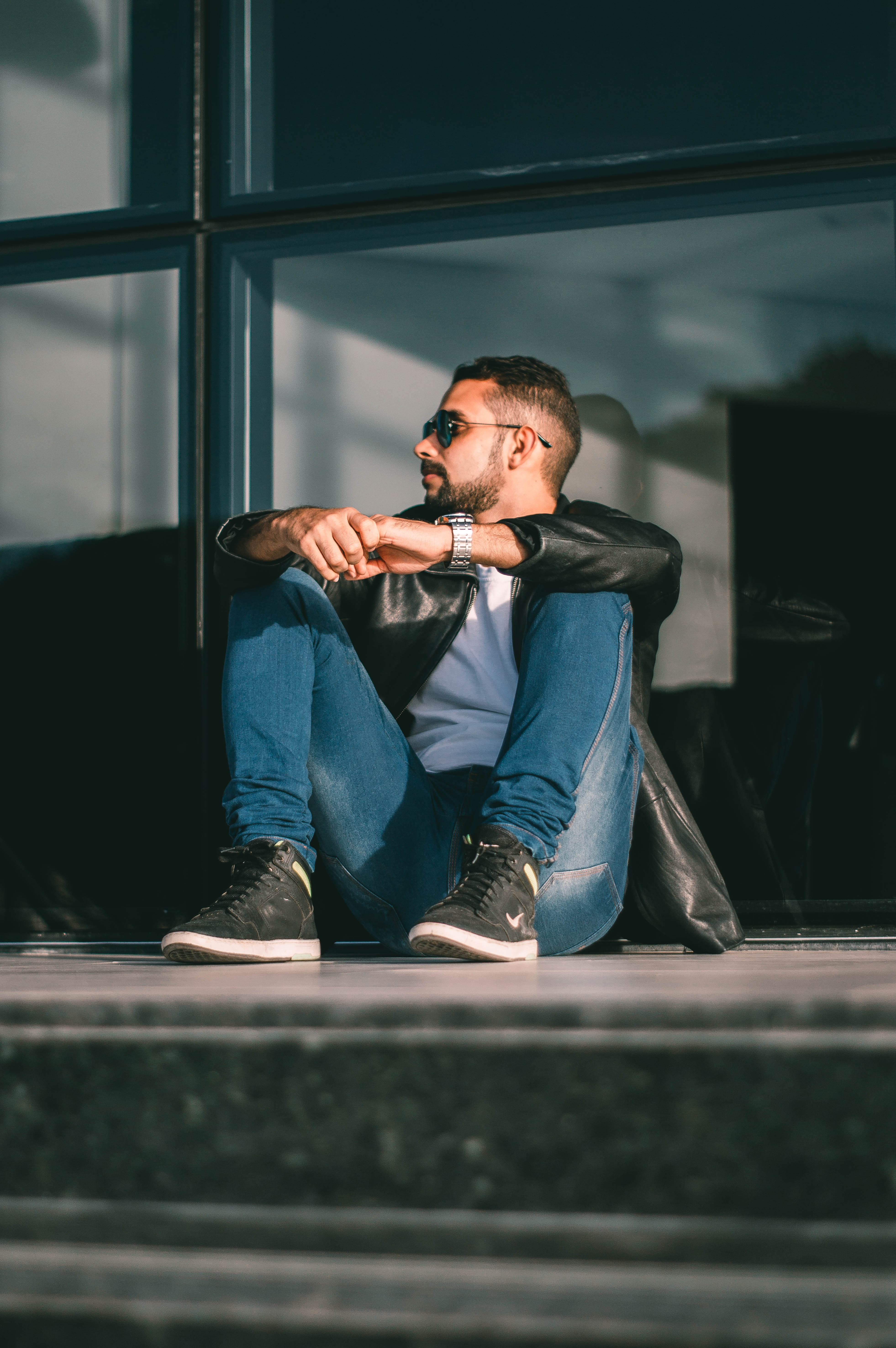 man sitting on floor leaning on glass wall inside room