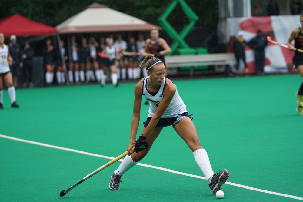 woman holding hockey stick on field