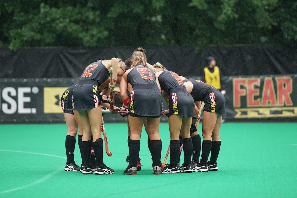 group of women team standing on green floor