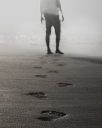 grayscale photography of man walking on sand leaving footprints