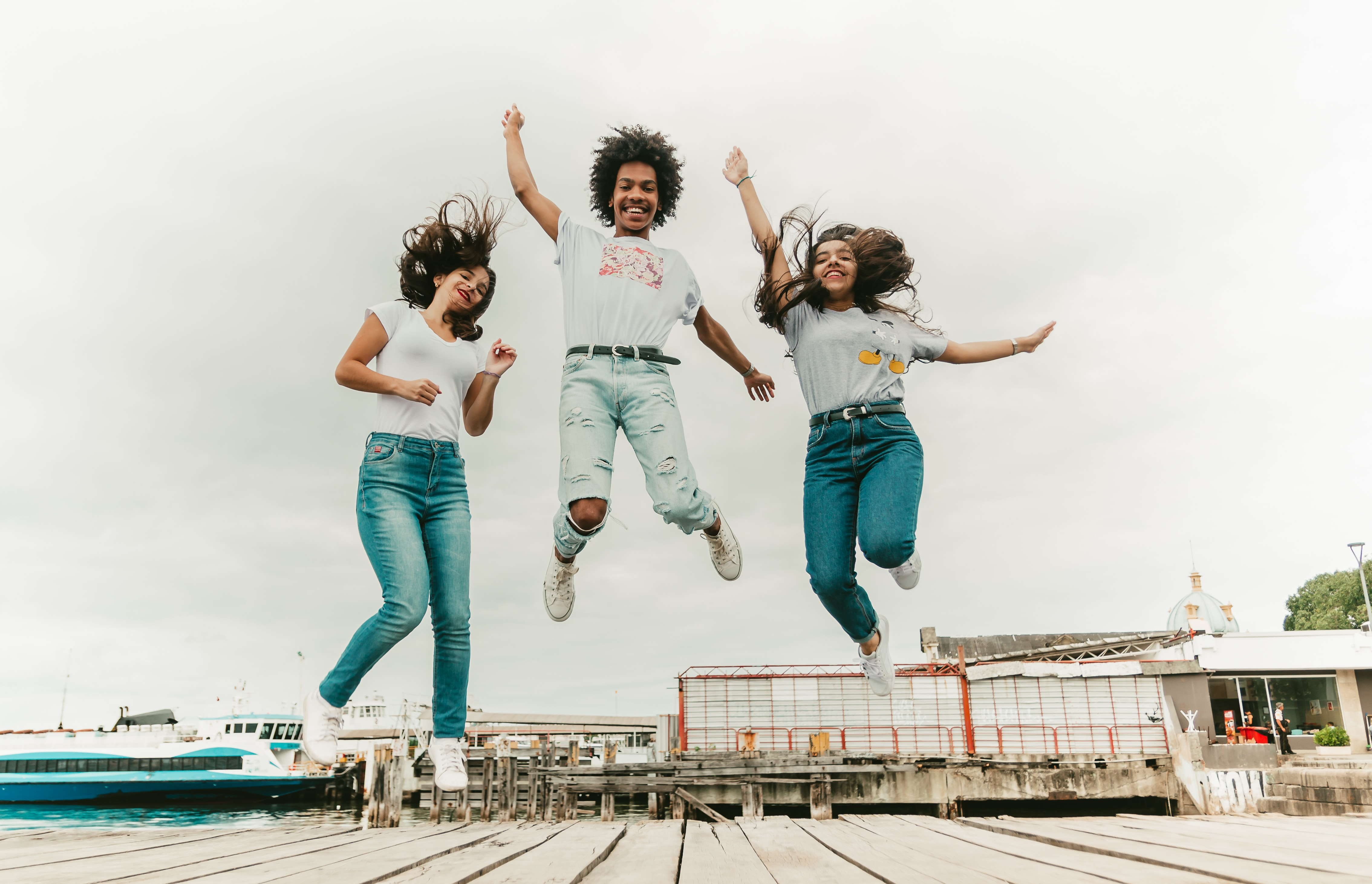 two women and one man jumping at daytime