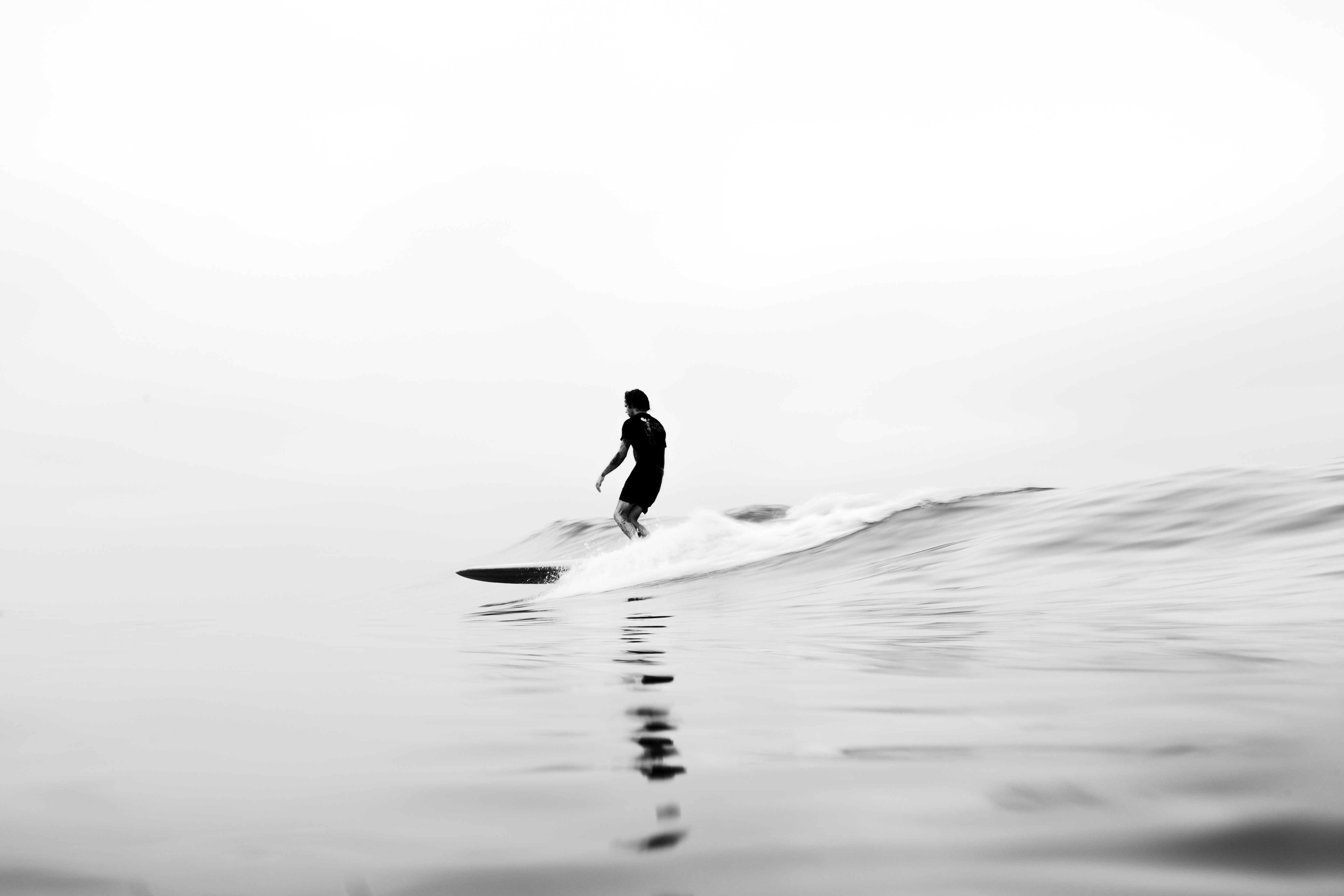 grayscale photo of man riding surfboard on water