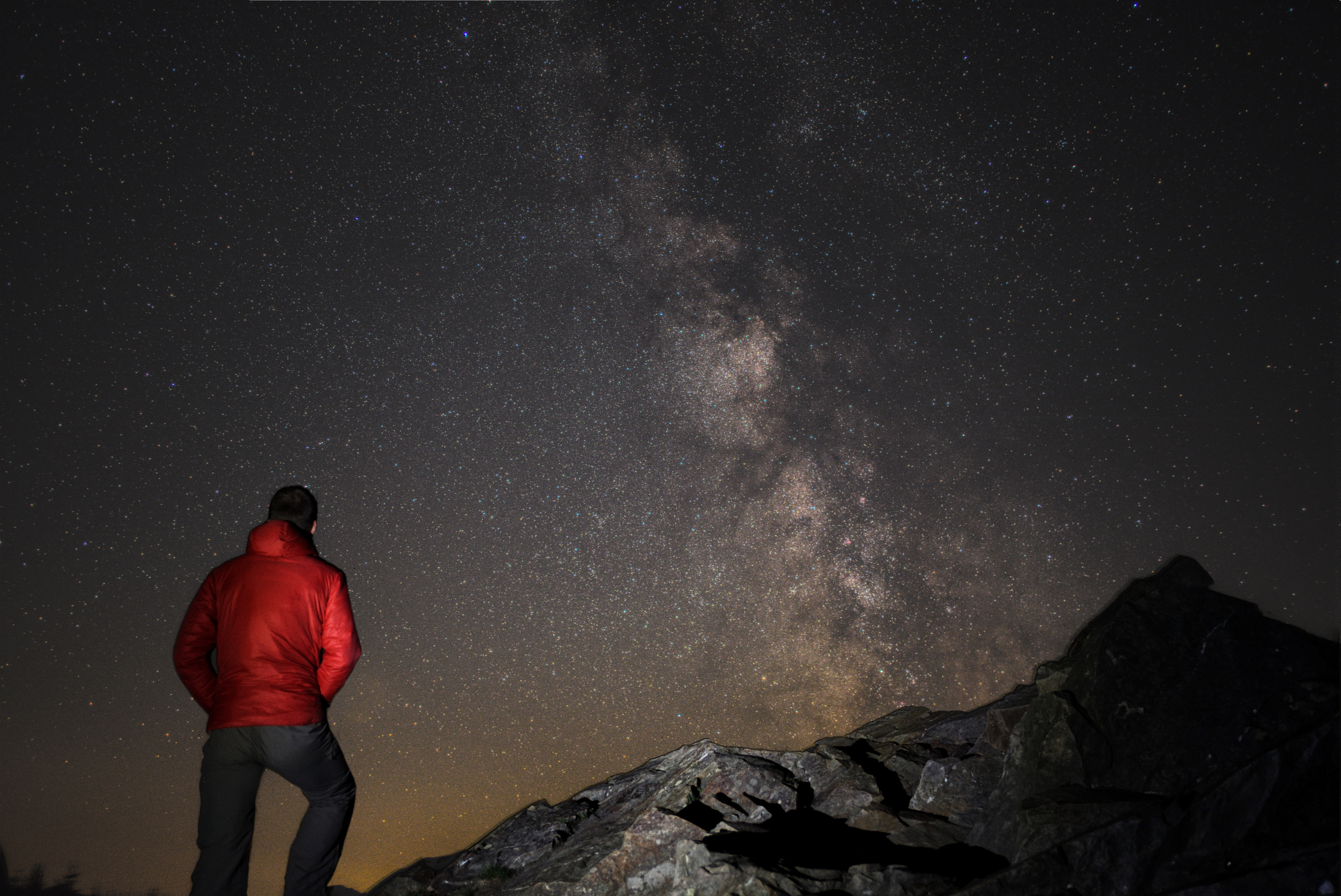 man wearing red jacket watching the milkyway