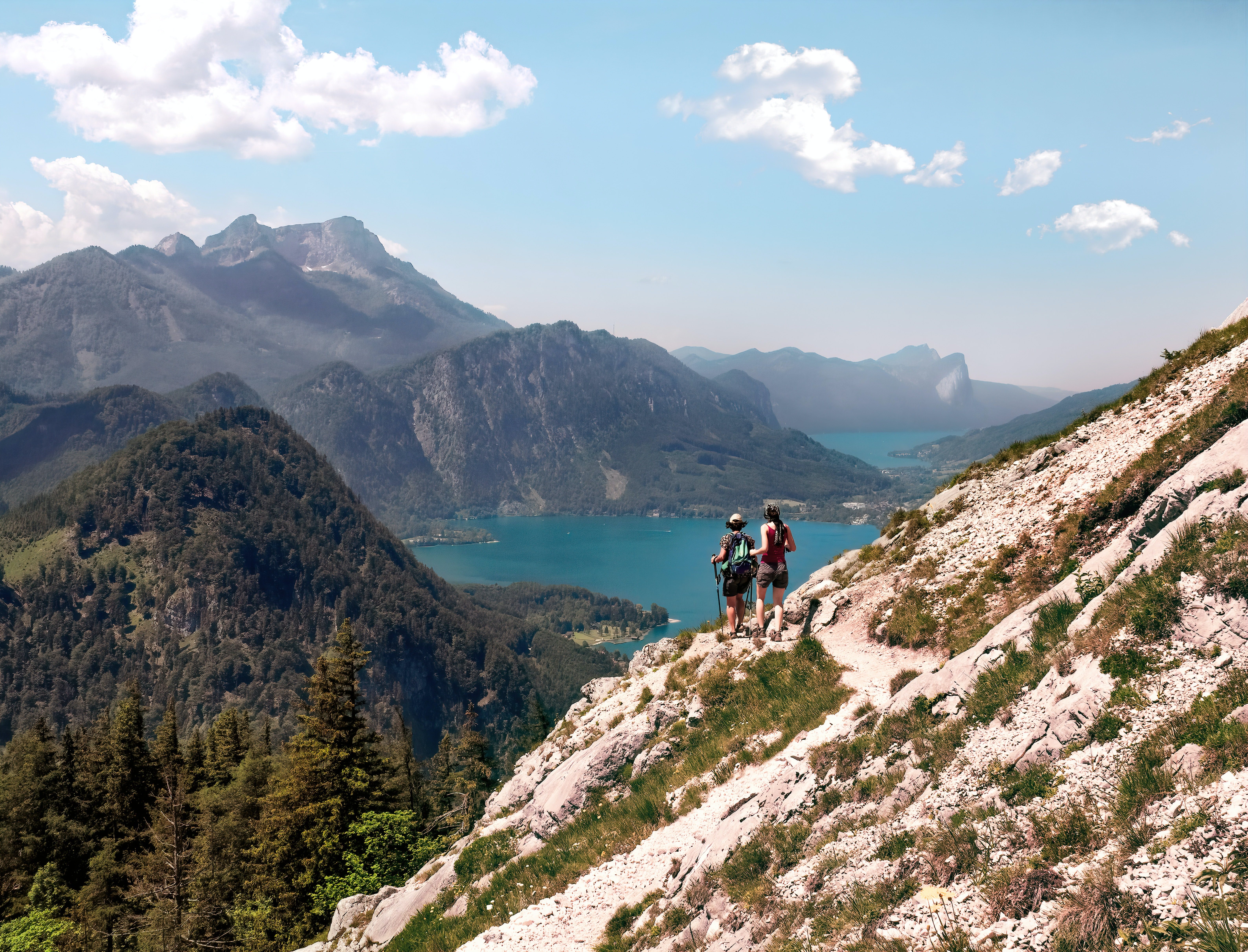 two person standing on mountain cliff