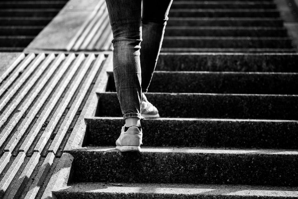 grayscale photo of person walking on steps