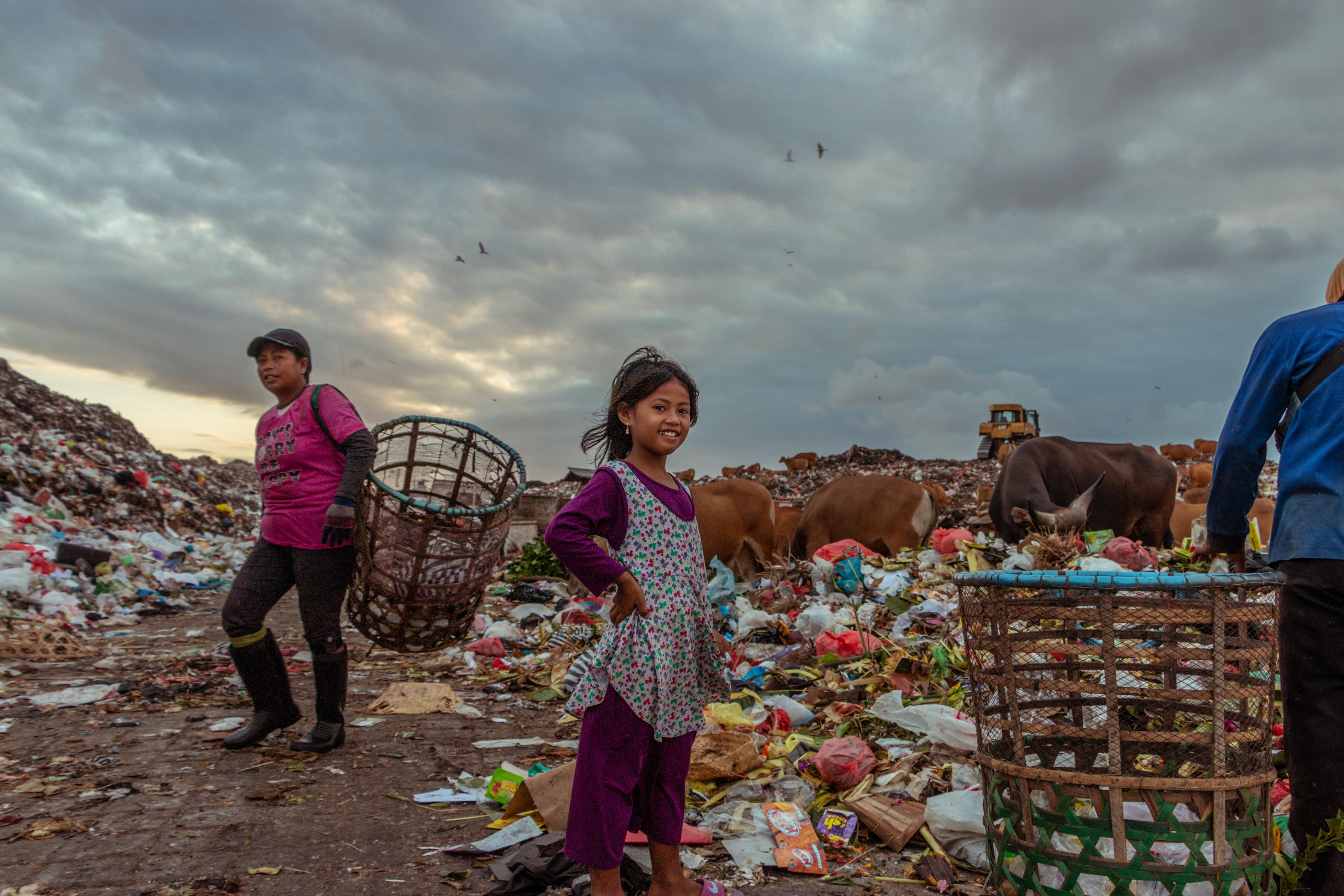 girl standing near garbage