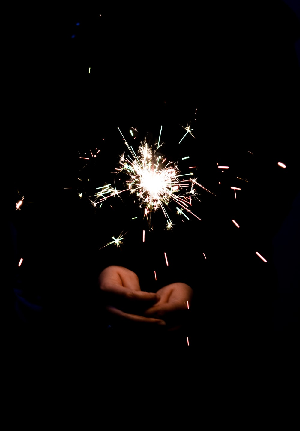 person holding sparkles