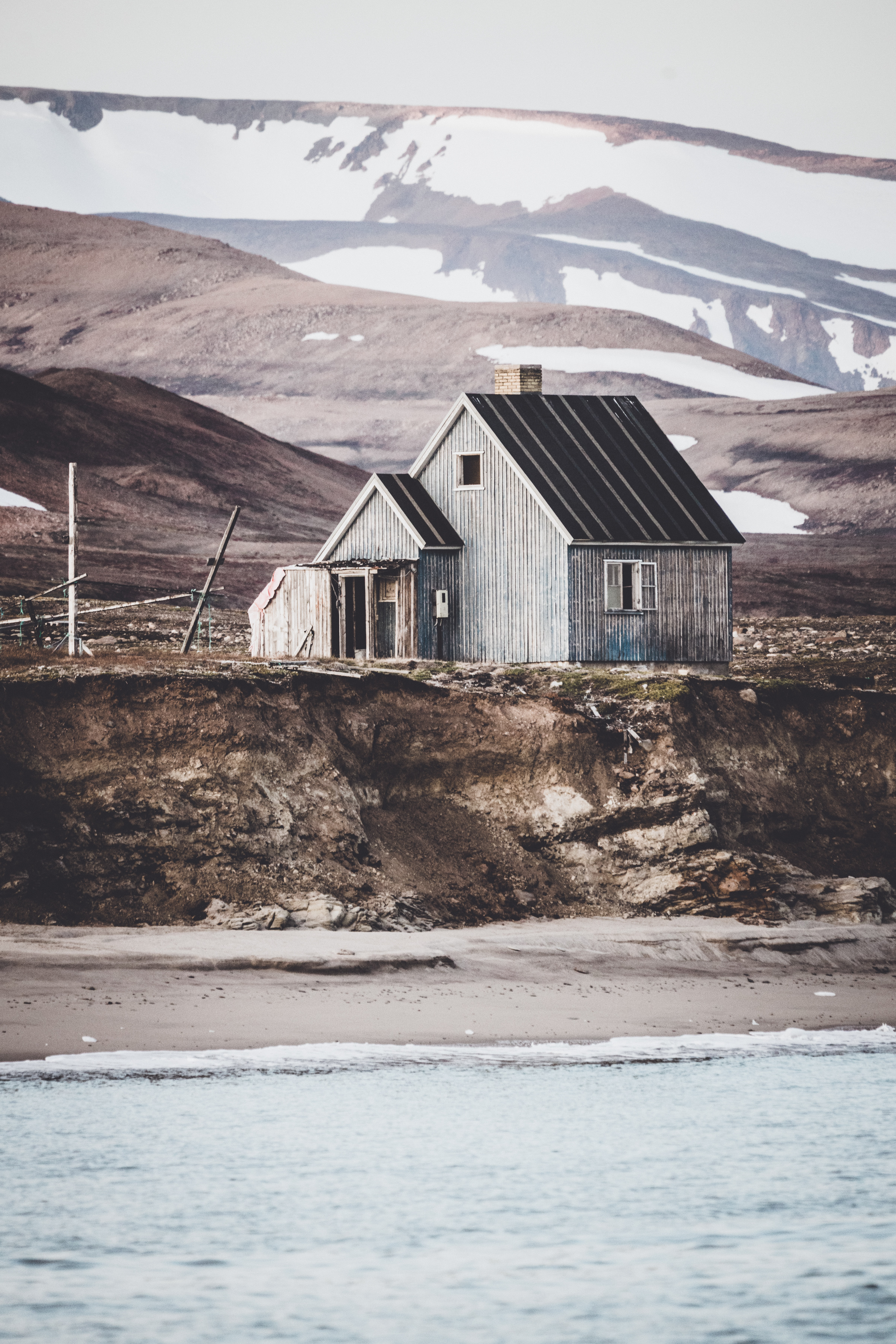 gray wooden house on land near body of water