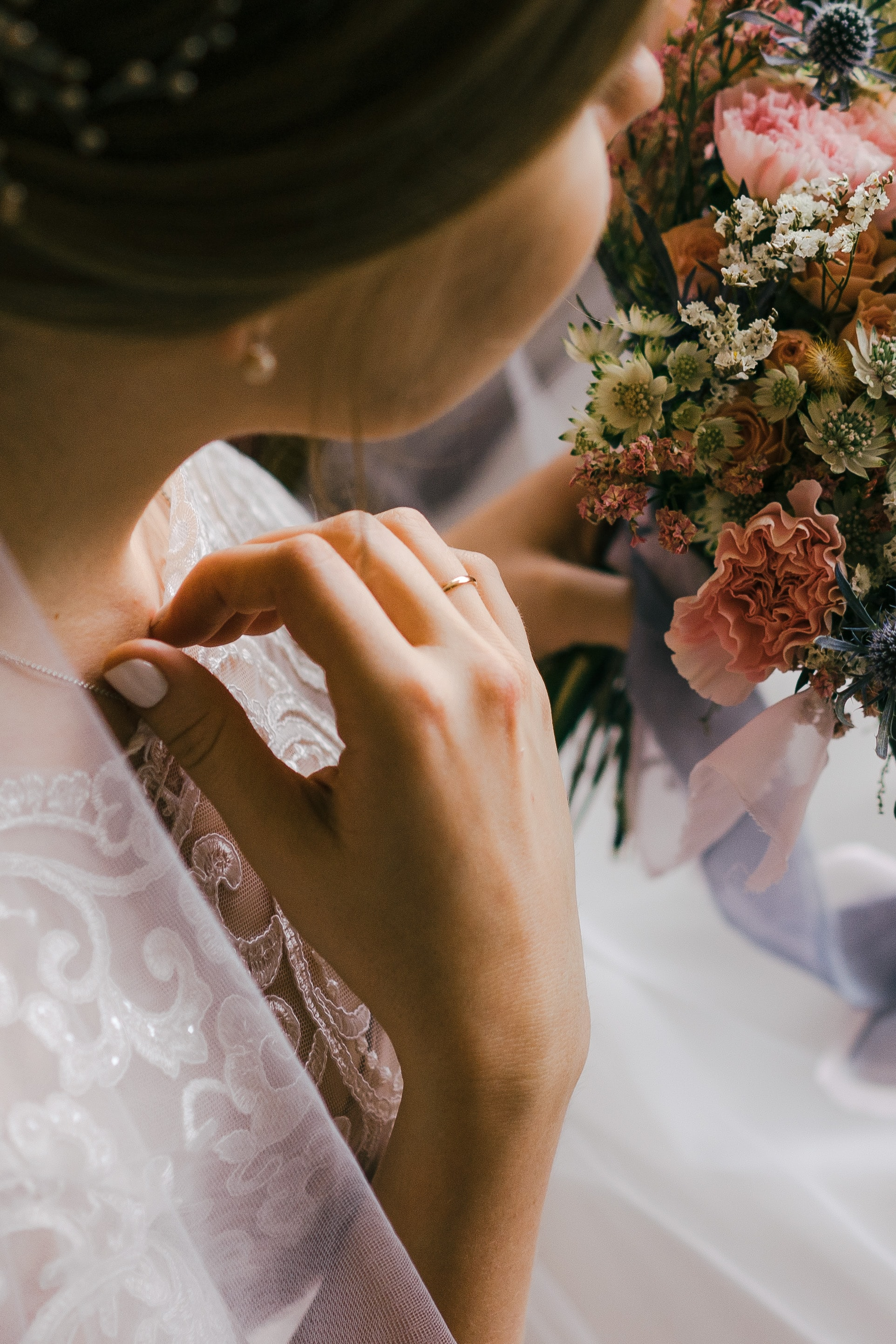 selective focus photography of woman in wedding dress holding flower