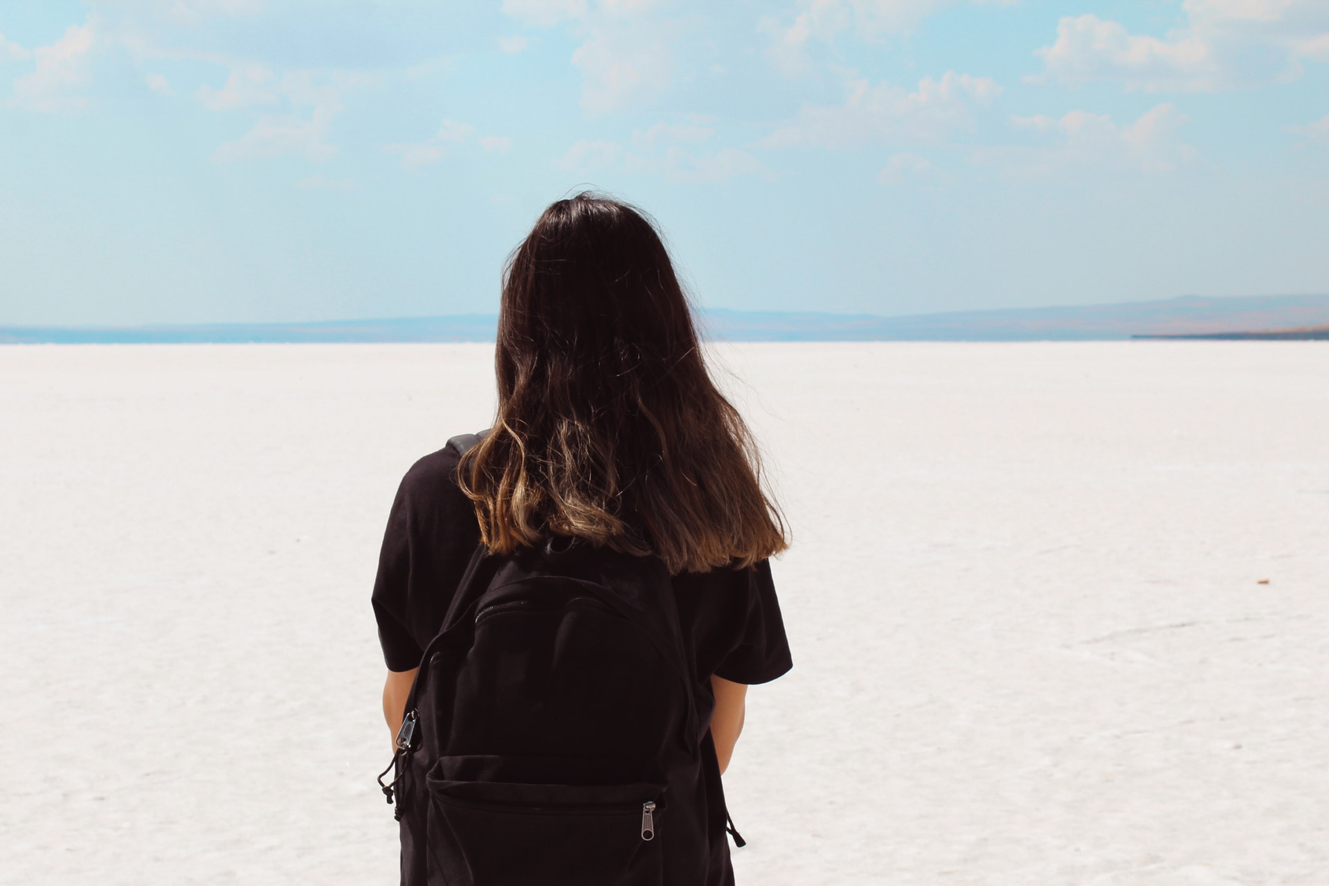 woman facing white field with backpack at daytime