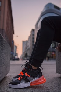 person wearing black-and-gray Nike Air Max 270 shoes