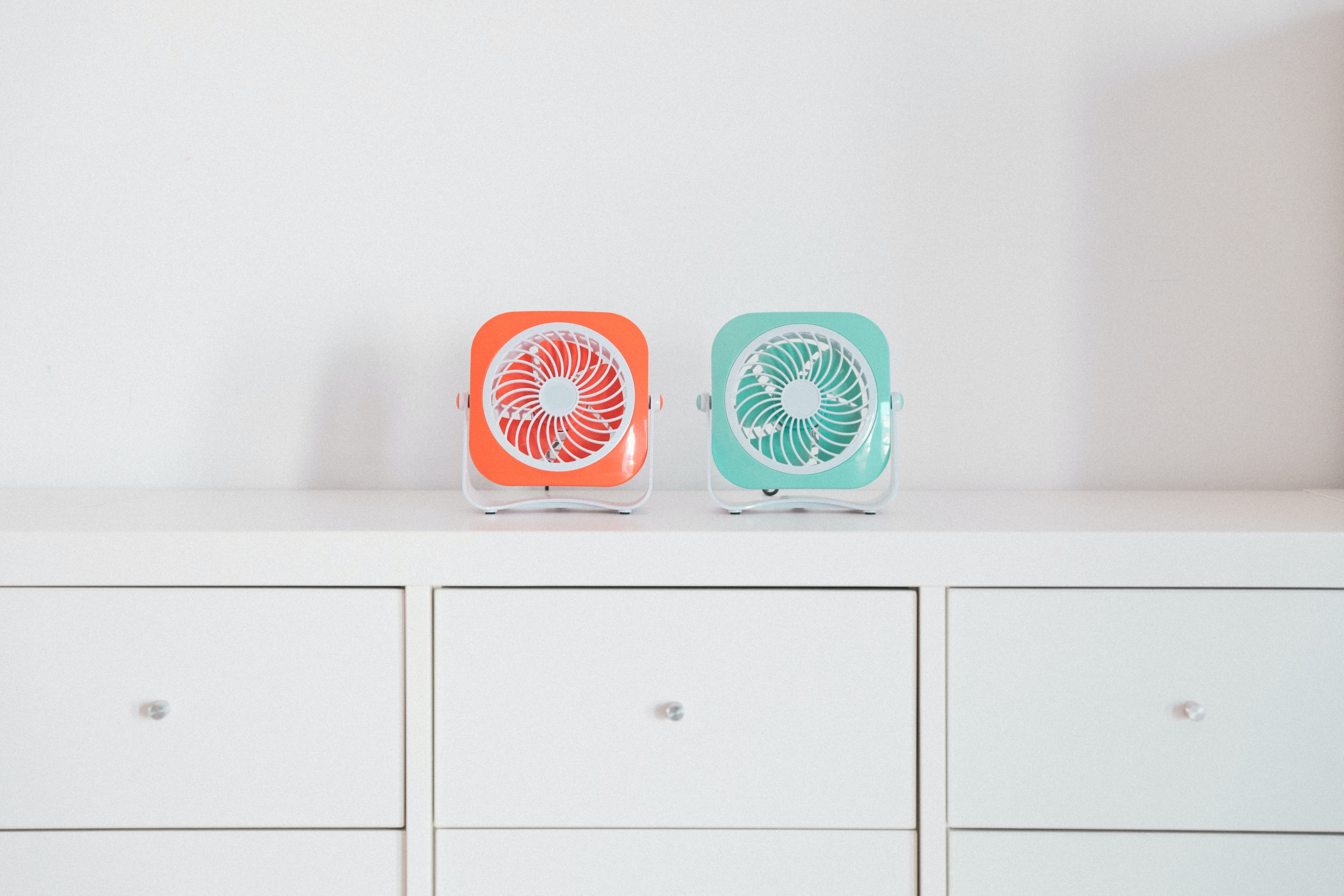 two red and green portable fans on white desk
