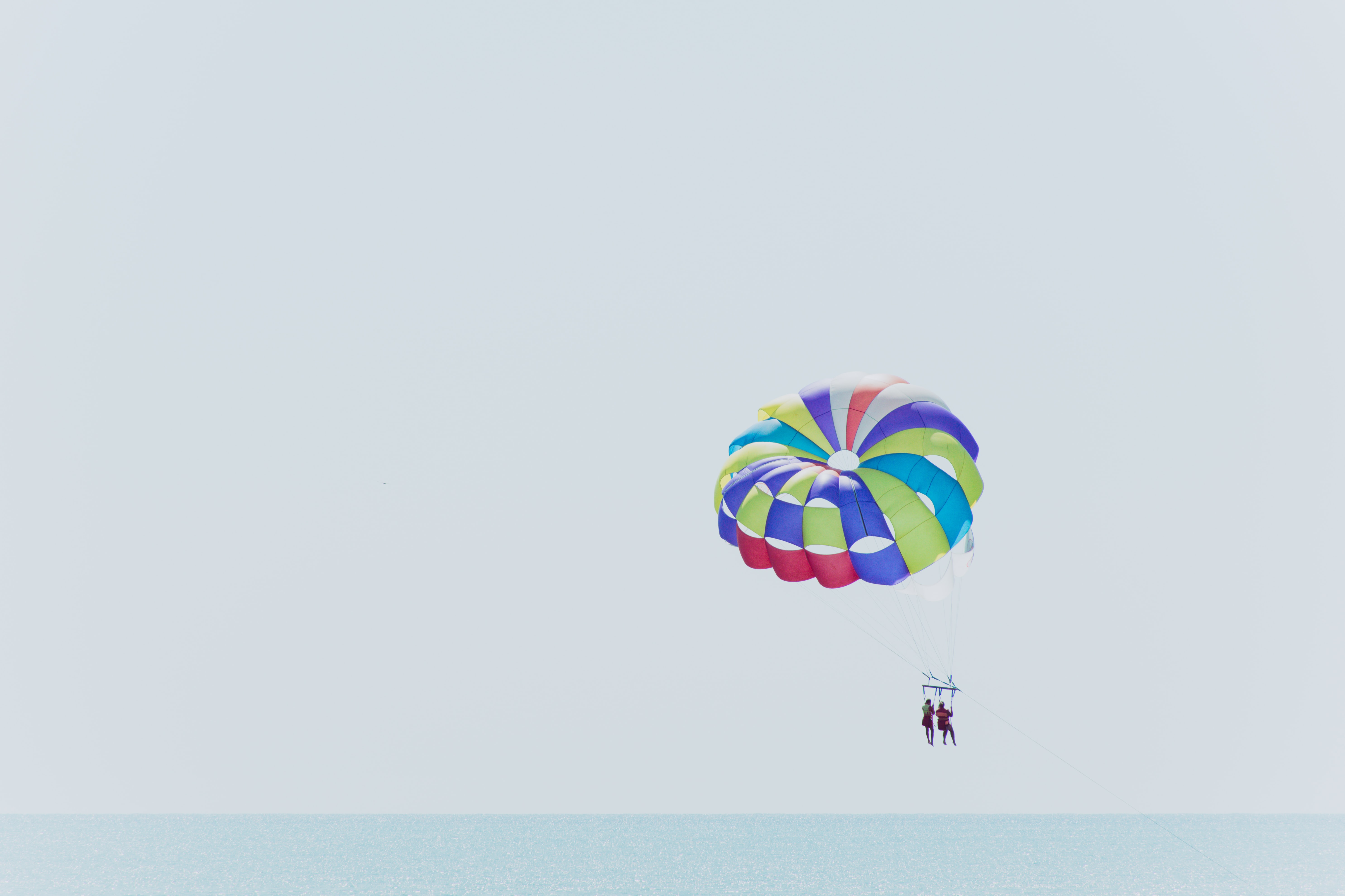 two people paragliding near ocean