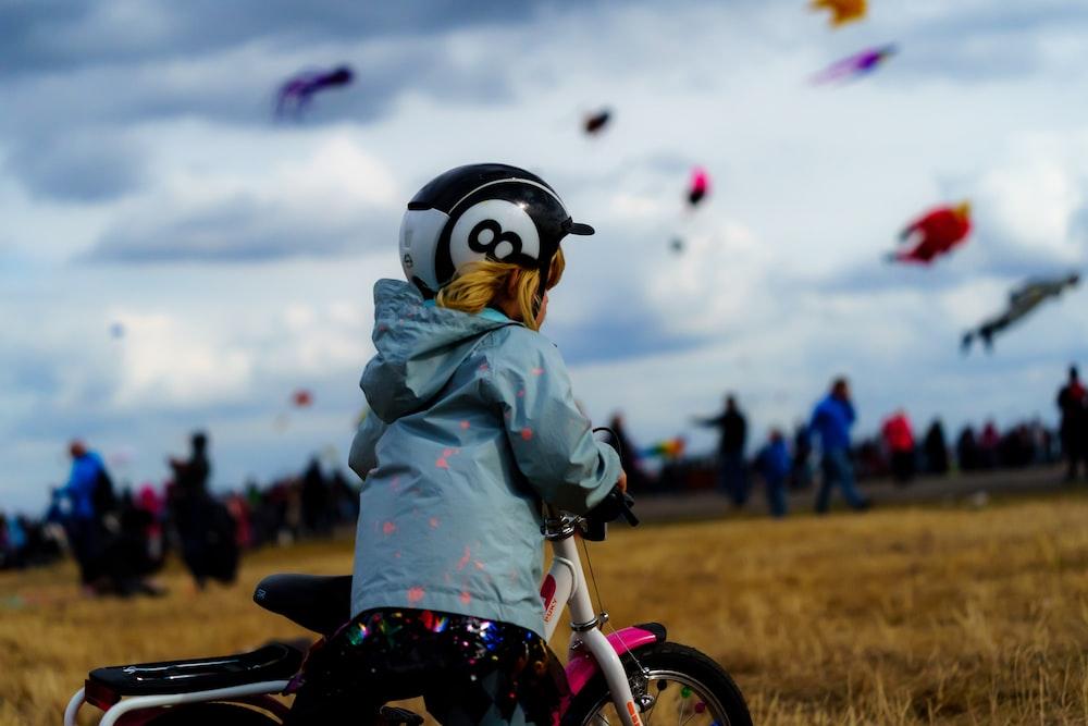 kid riding bike outdoors selective focus photography