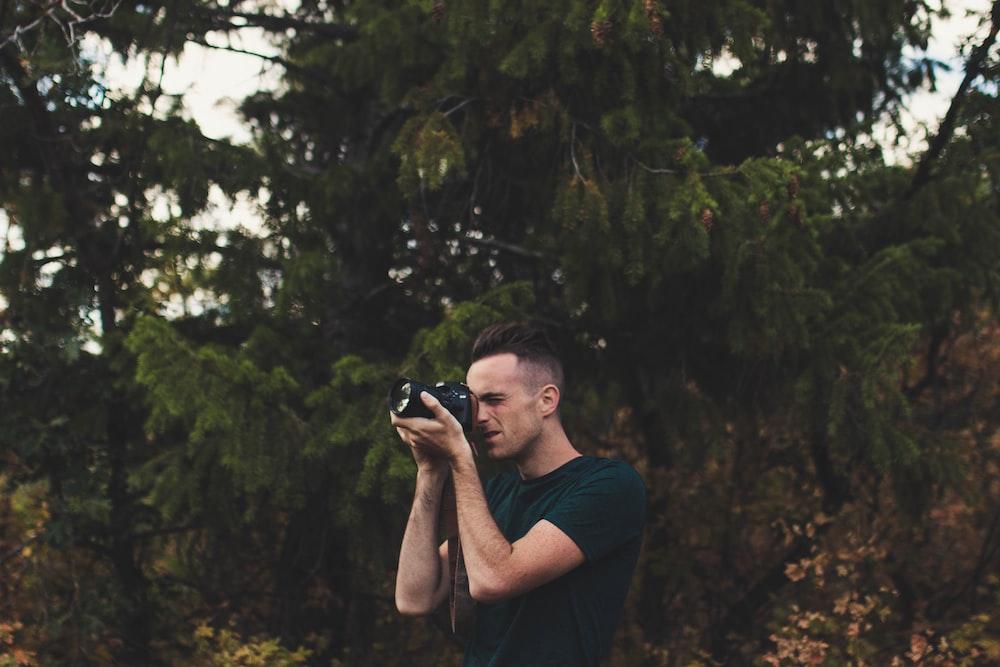man capturing photo using DSLR camera
