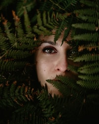person's face covered with fern plant