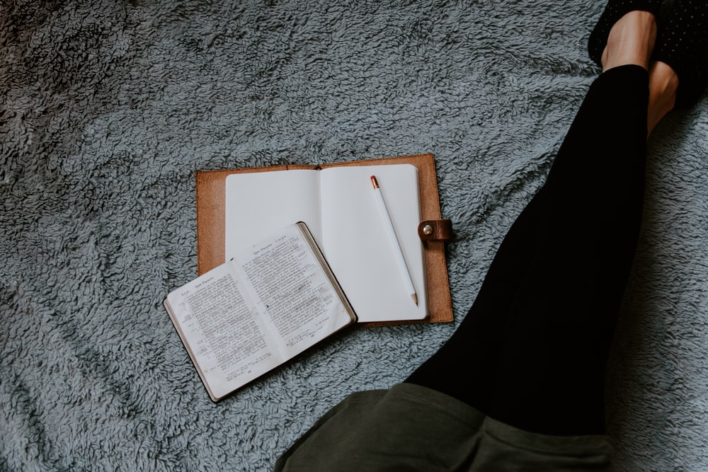 opened white book placed near woman leg on grey surface