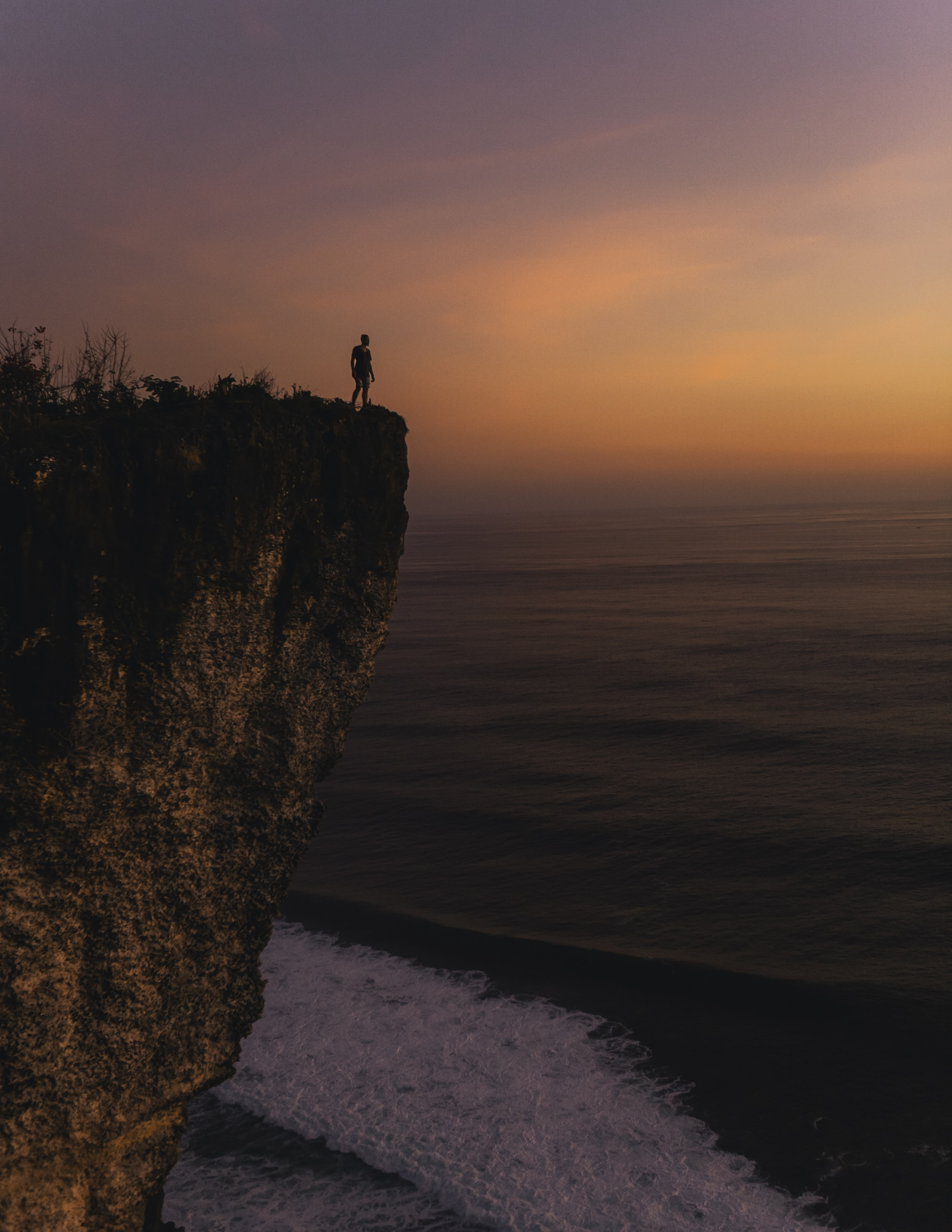 person standing on cliff during sunset