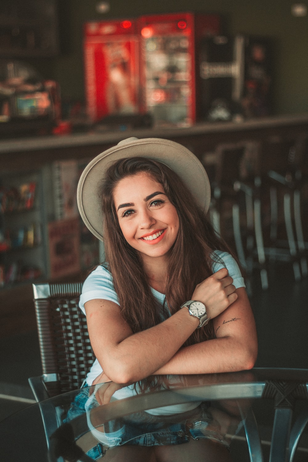 woman sitting while smiling and wearing hat