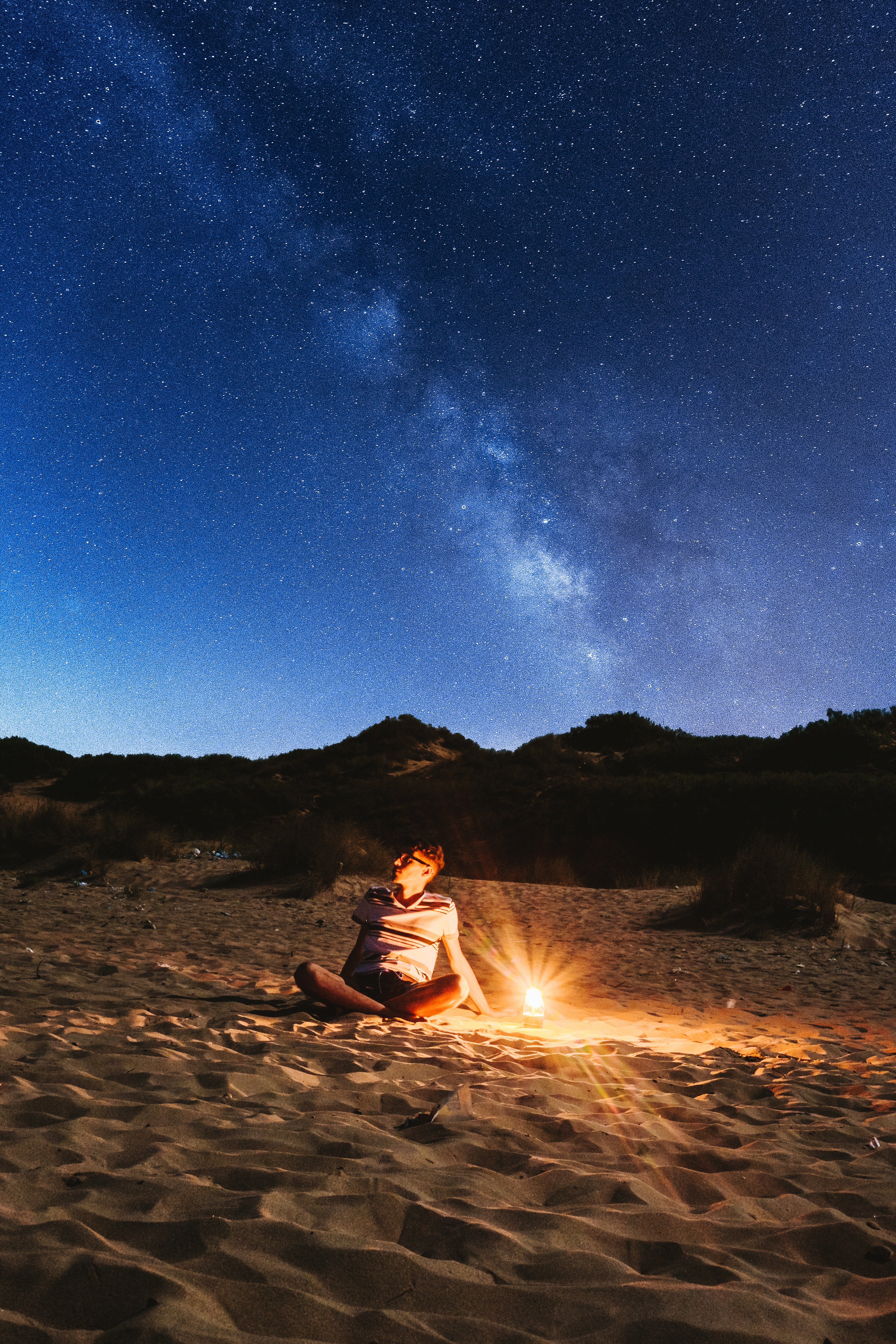 sitting man near lamp looking on the sky with milky way