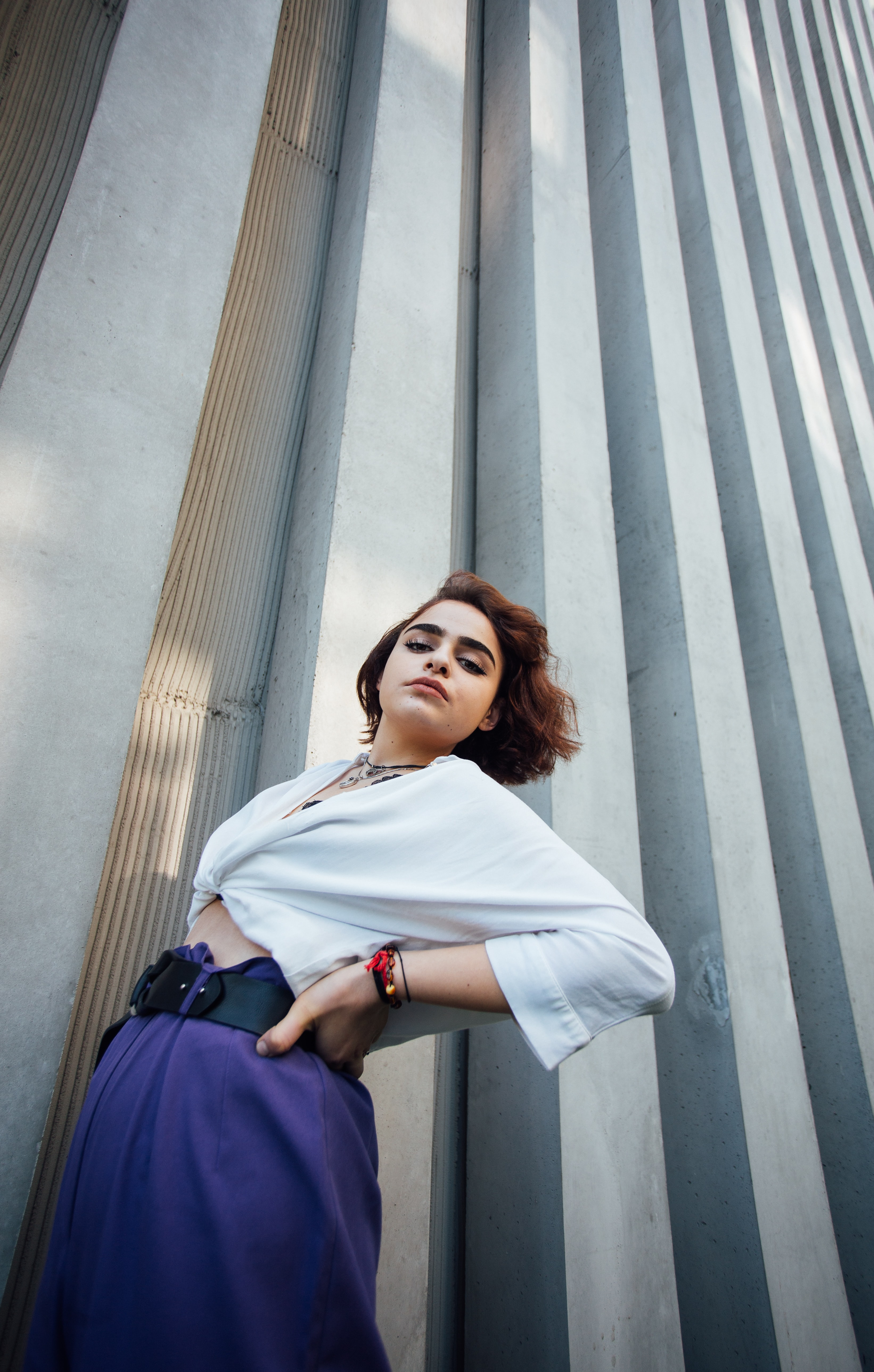 woman standing beside gray concrete building structure