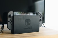 black Nintendo Switch with JoyCon beside flat screen TV