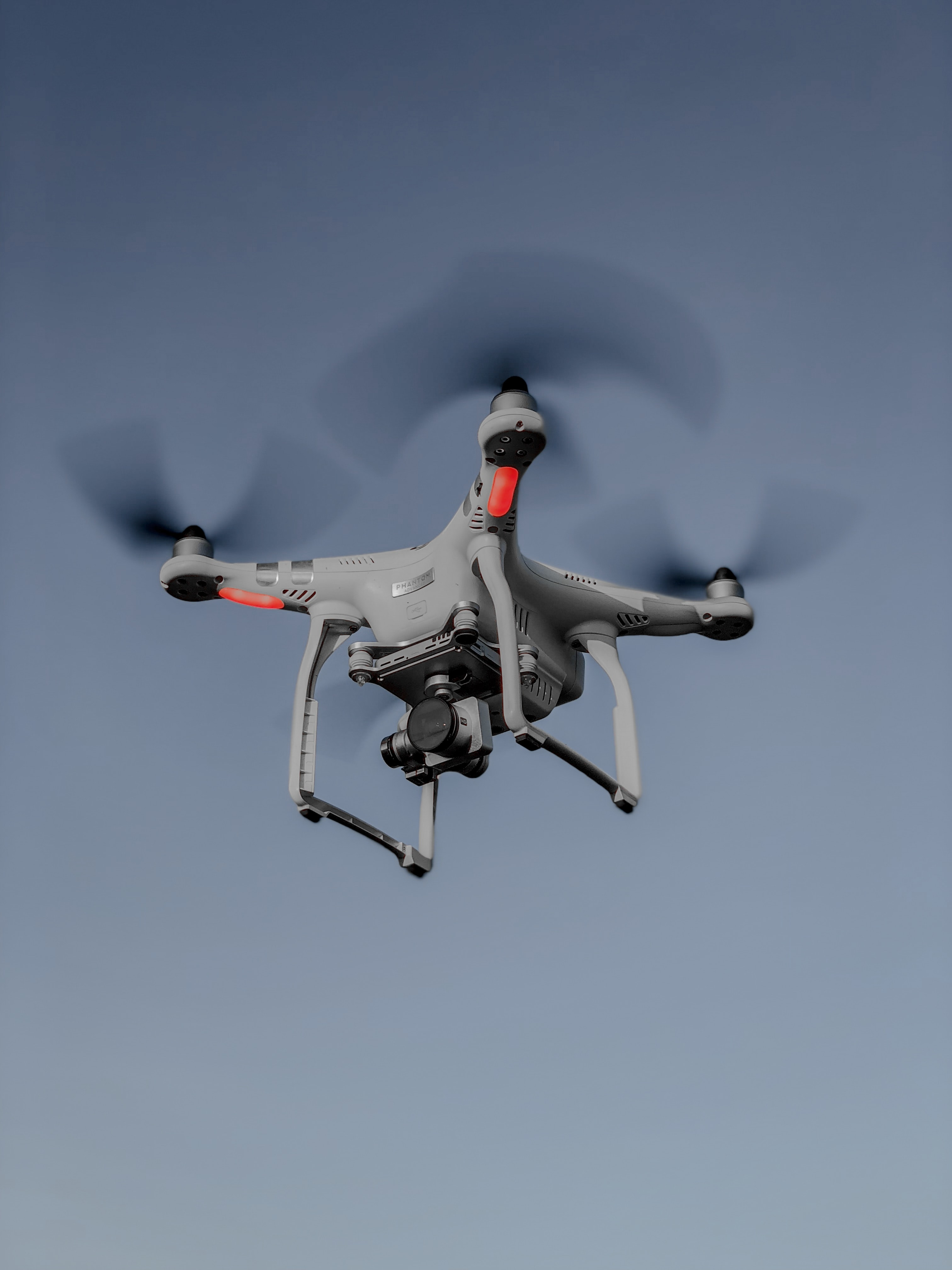 photo of flying white and red quadcopter drone