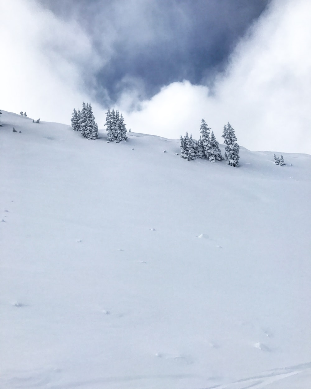 photo of mountain covered by snow under cloudy sky