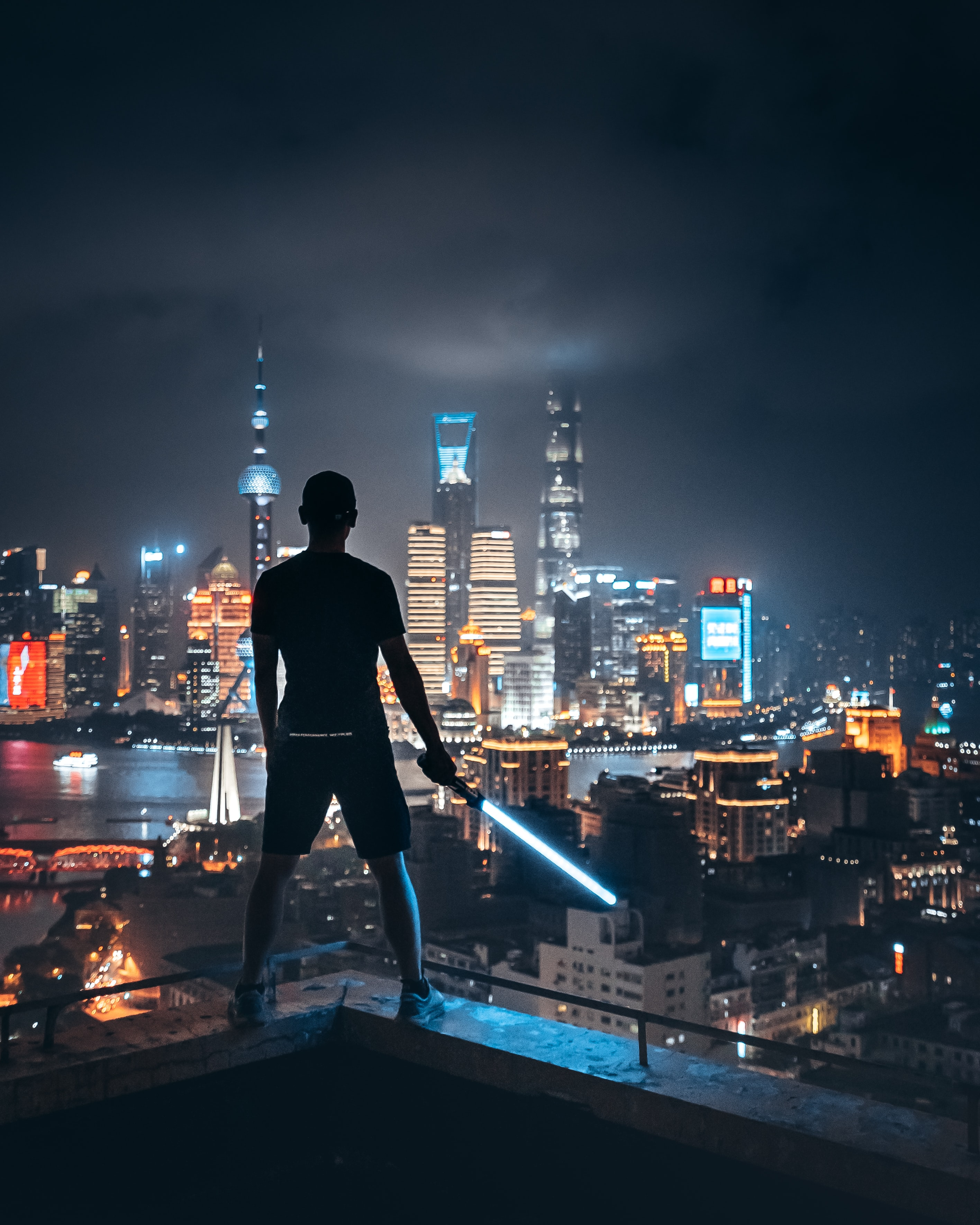 man holding lightsaber while standing on ledge overlooking city