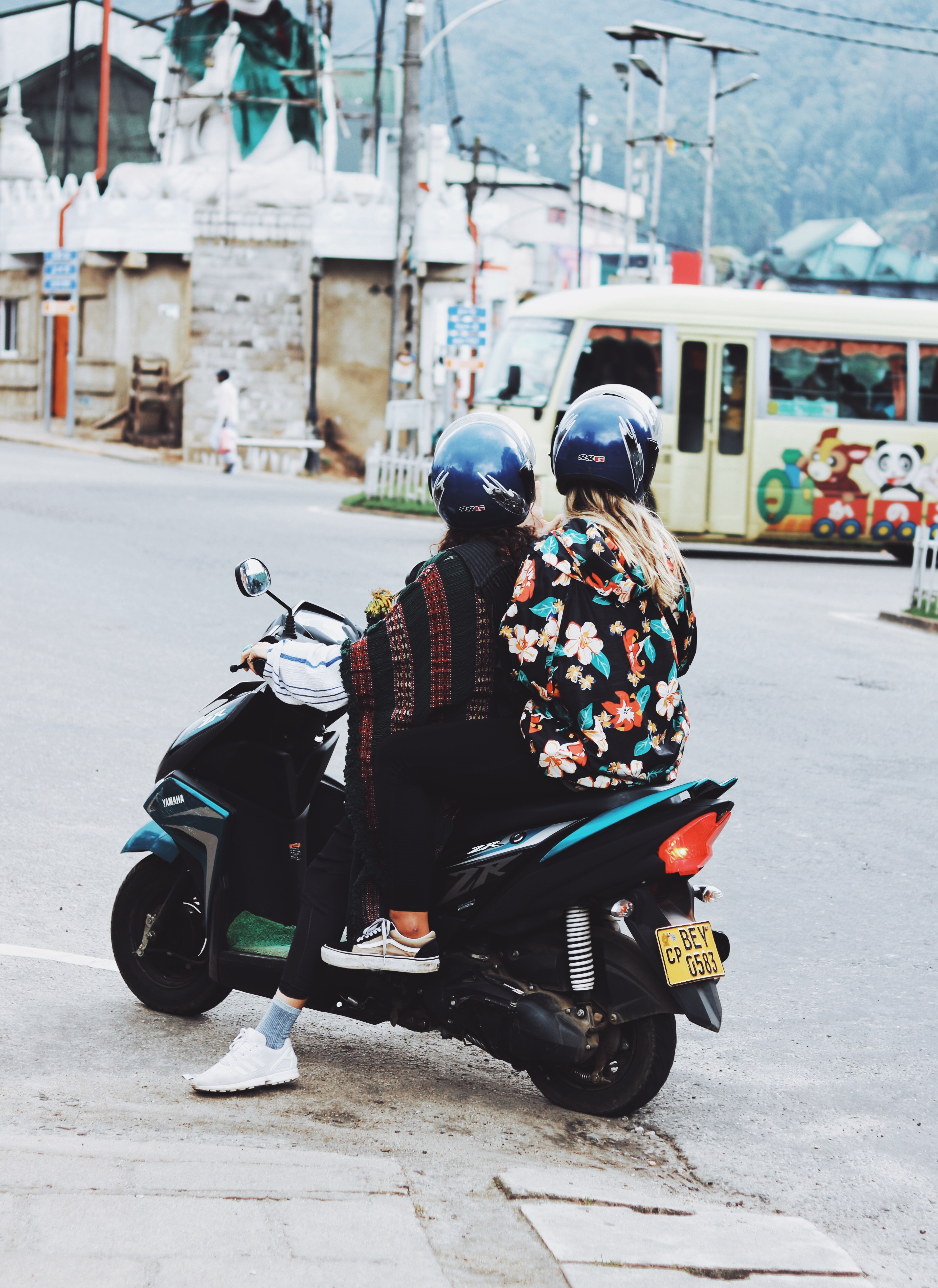 two person riding motor scooter