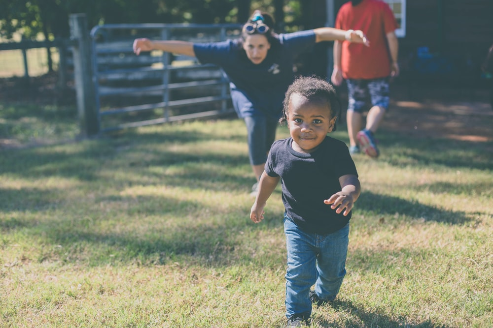 toddler walking on green grass field at the back of woman rushing