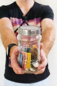 man holding clear glass jar