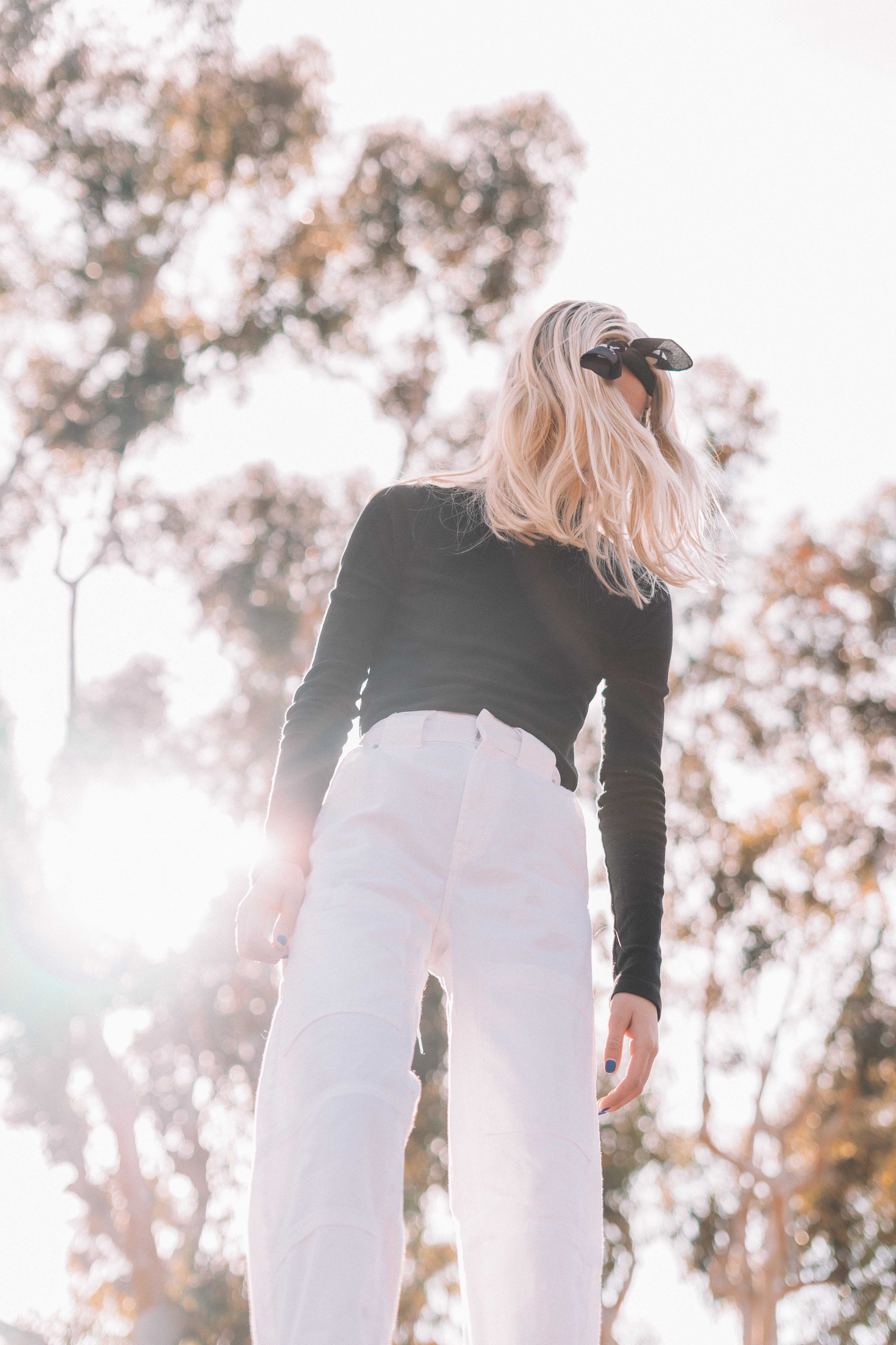 woman in black long-sleeved shirt and white pants