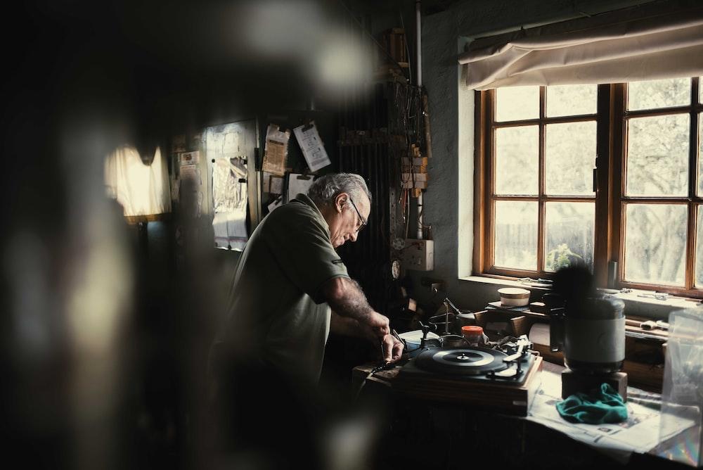man holding handheld tool standing beside window