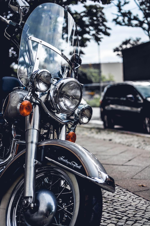 gray touring motorcycle parked on sidewalk at daytime