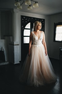 woman in beige dress standing in white room