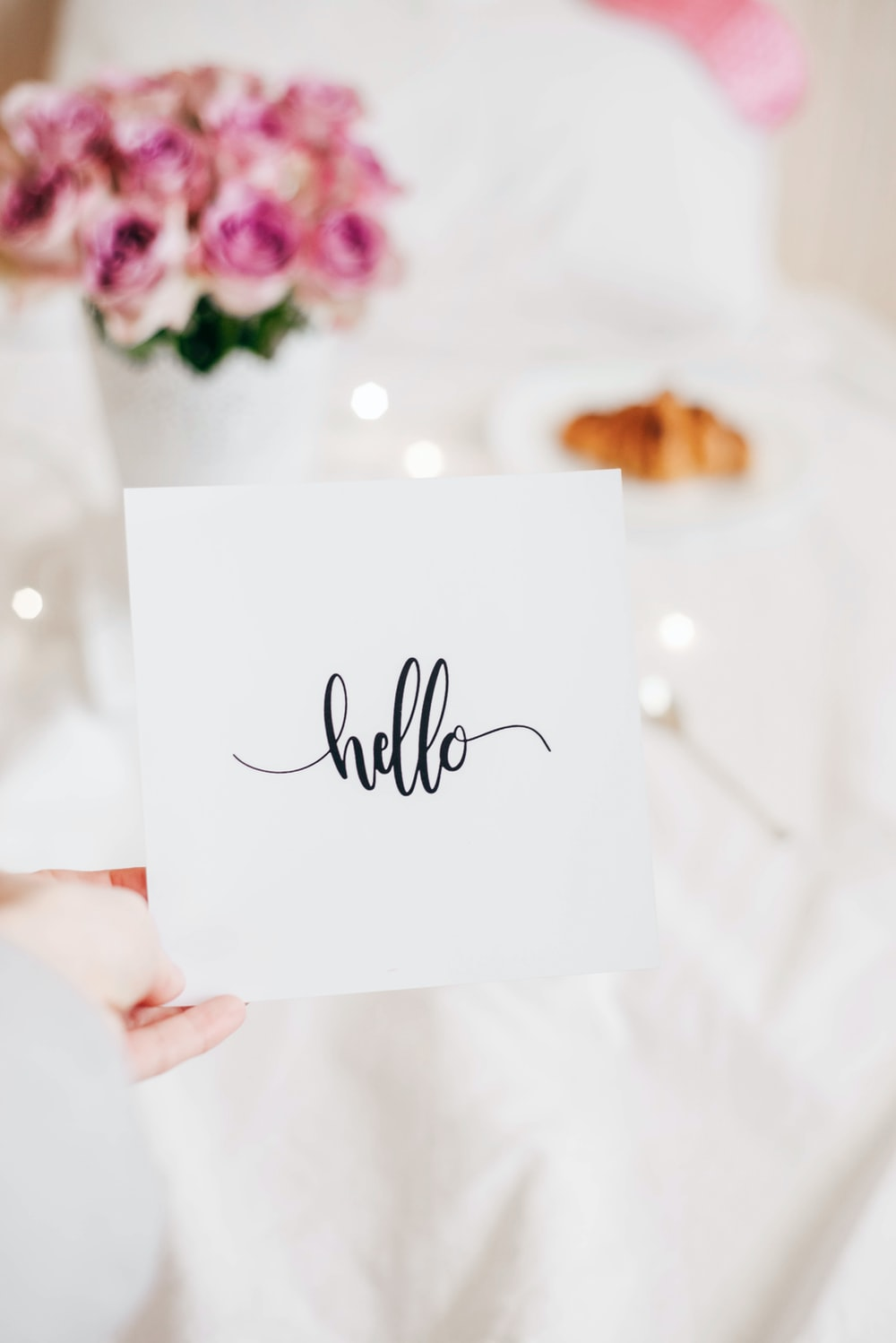 person holding hello note