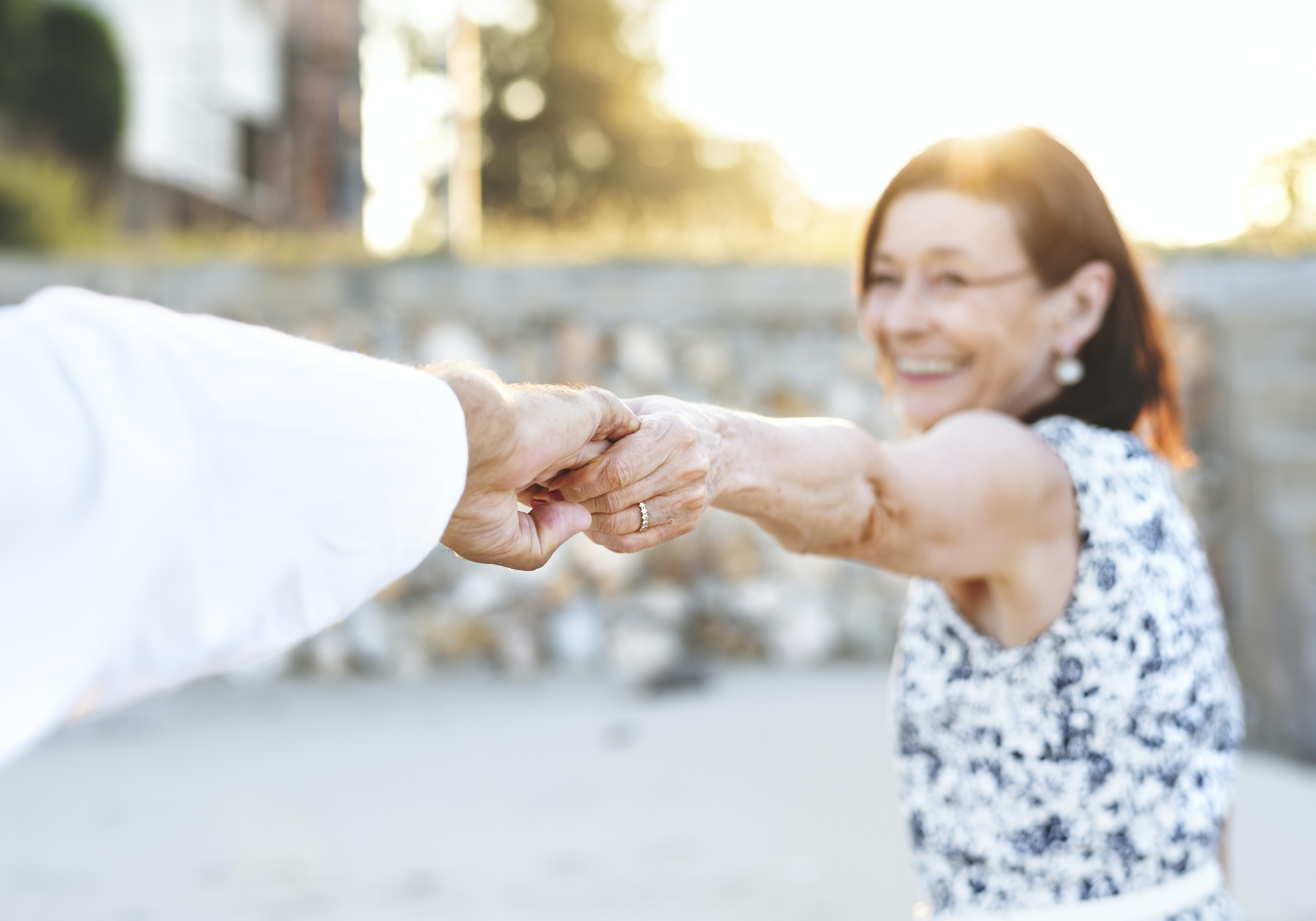 smiling woman while holding hands during daytime