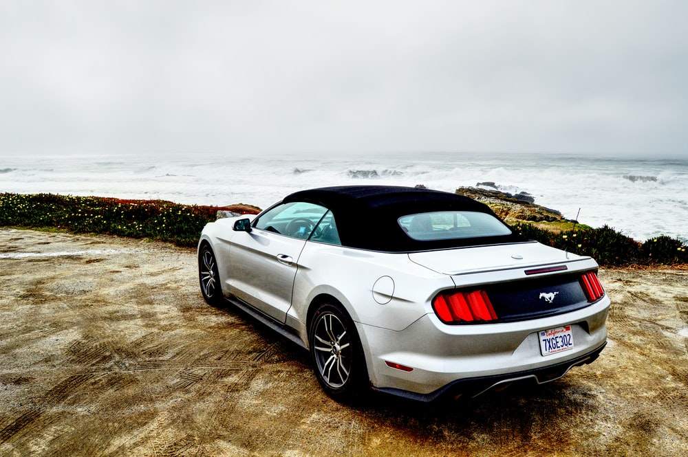 gray coupe parked near seashore