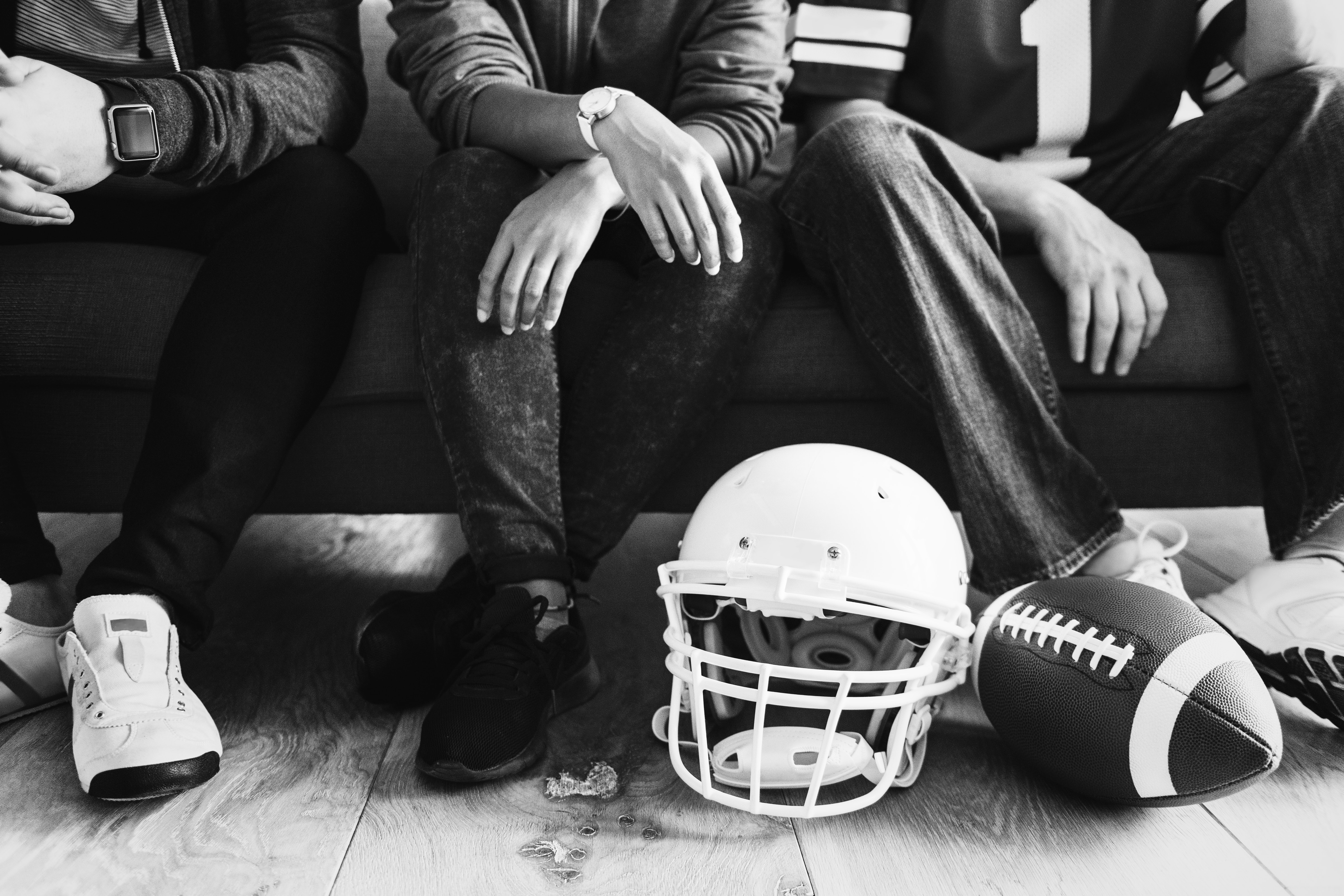 grayscale photo of people sitting on bench near football helmet