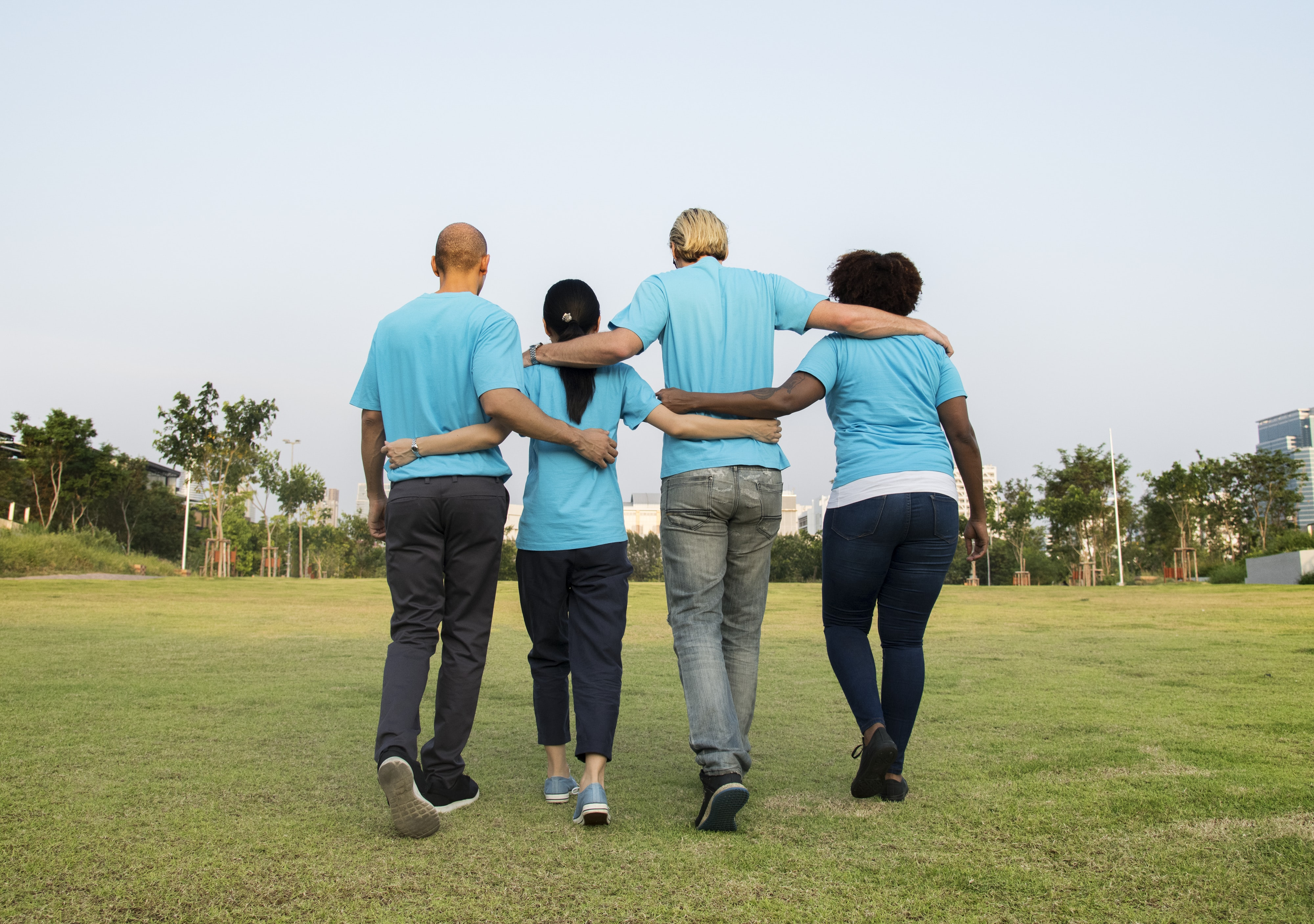 two men and two women wearing teal shirts holding each others back at daytime