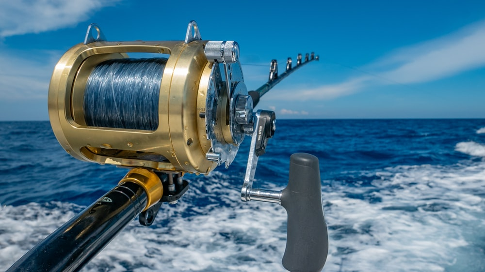 fishing reel by water during daytime