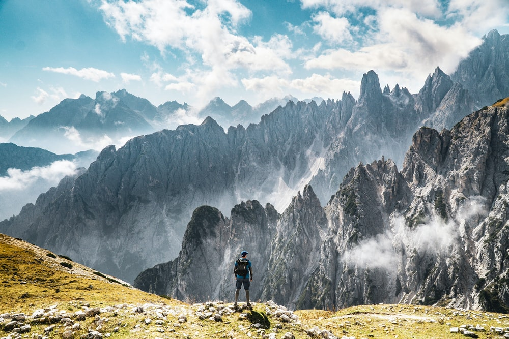 person standing on green-grassed mountain facing grey rocky mountains covered by clouds during daytime
