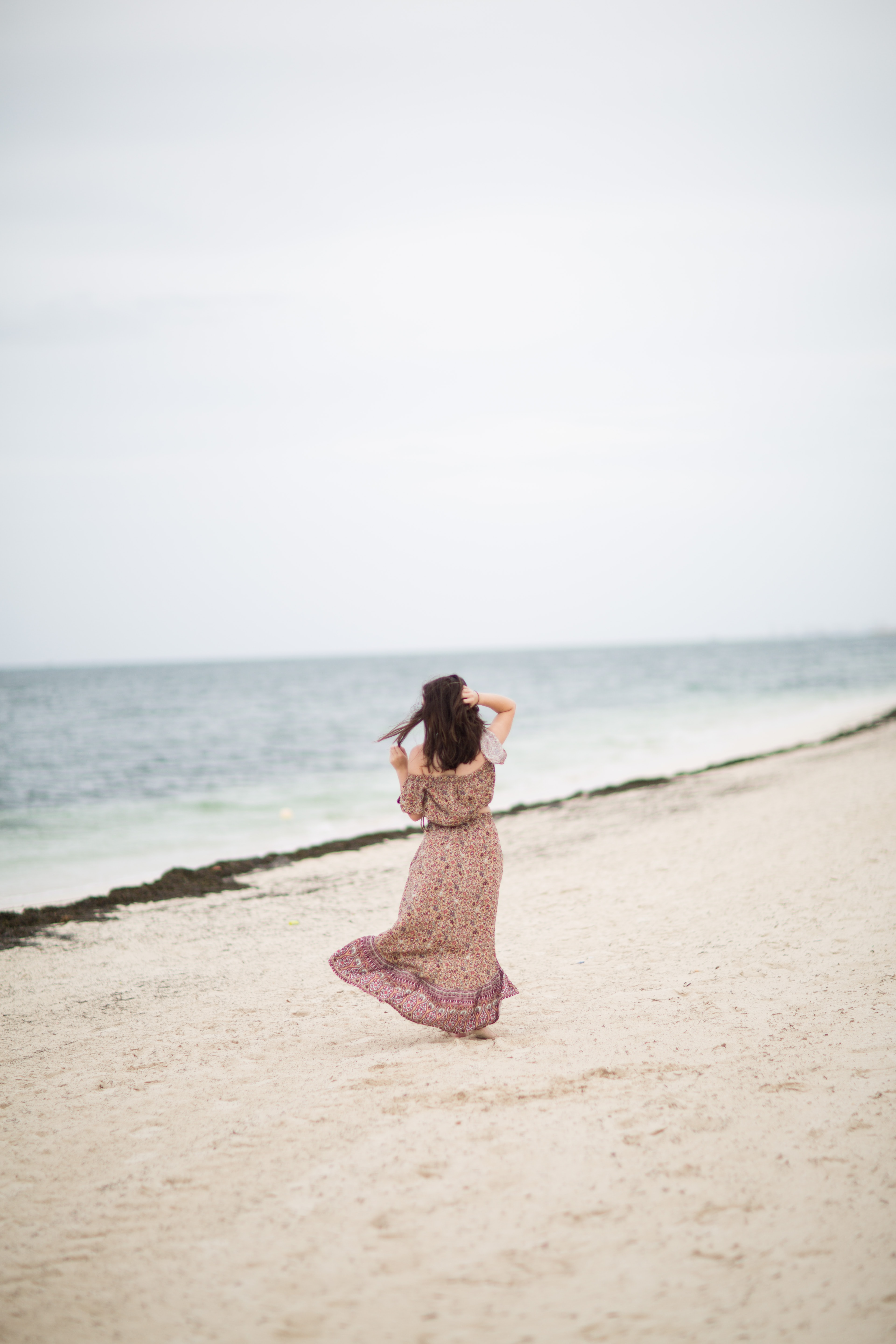woman standing on beach during daytime
