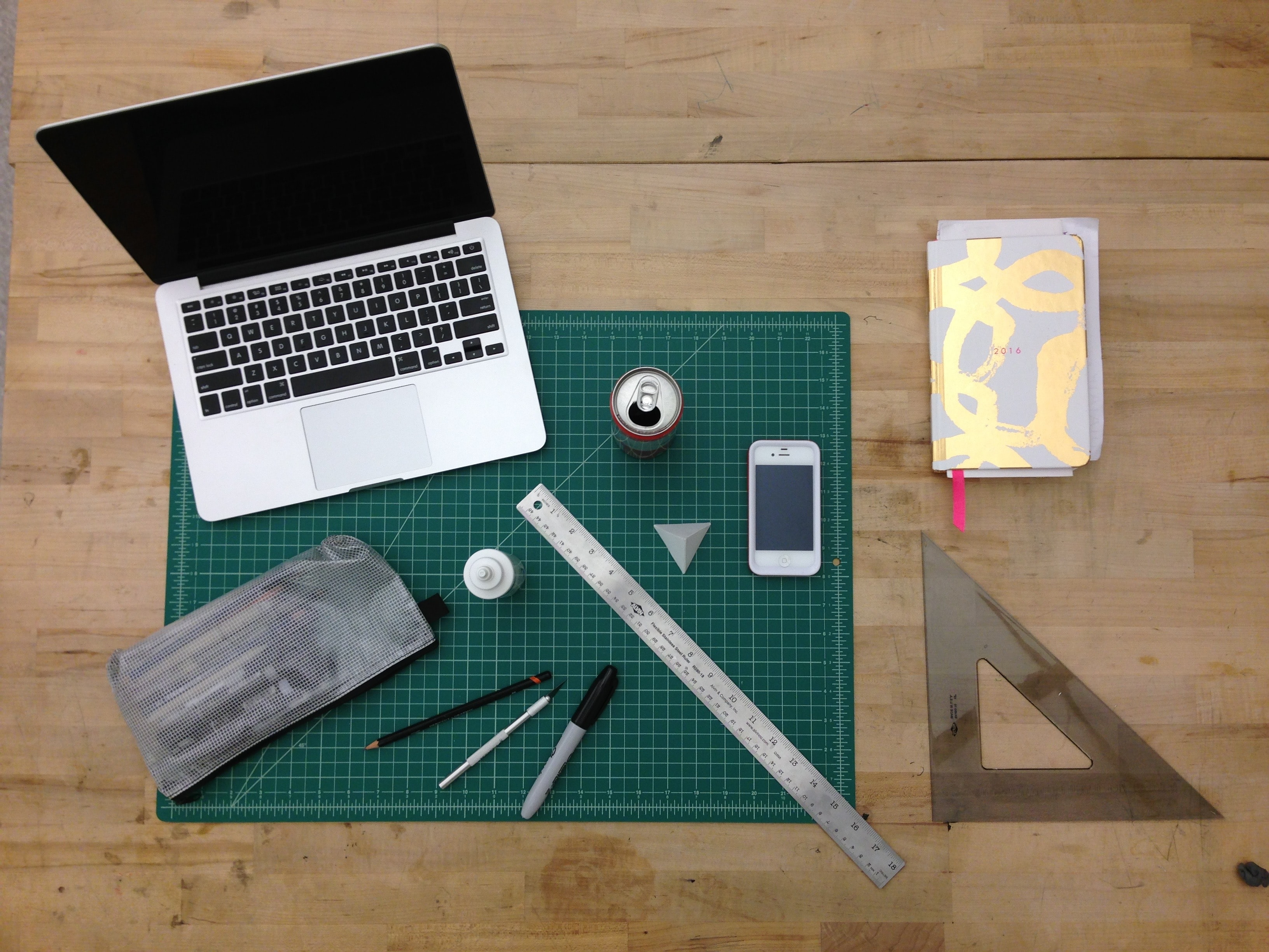 flat lay photography of MacBook, ruler, and can