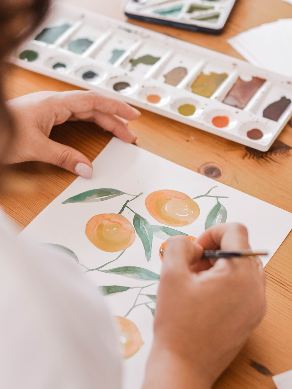 person painting a orange fruits
